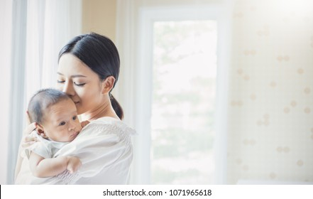 Close up portrait of beautiful young asian mother kissing her newborn baby in hospital. Healthcare and medical love asia woman lifestyle mother's day concept with copy space.