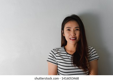 Close up portrait of a beautiful young asian woman smiling on wall background.