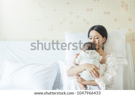 Close up portrait of beautiful young asian mother with newborn baby, copy space with bed in the hospital. Healthcare and medical love lifestyle mother's day concept