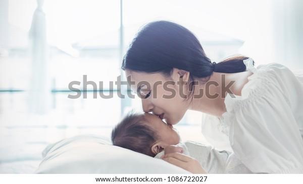 生まれたばかりの赤ちゃんにキスをする美しいアジアの若い母親の接写。医療と医療。アジア人の女の子は、ライフスタイルが大好きです。アジア母の日のコンセプトバナー