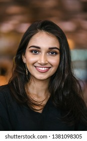 A close up portrait of a beautiful, young, attractive and photogenic Indian Asian girl during the day in the city. She is wearing a casual black dress and smiling radiantly.