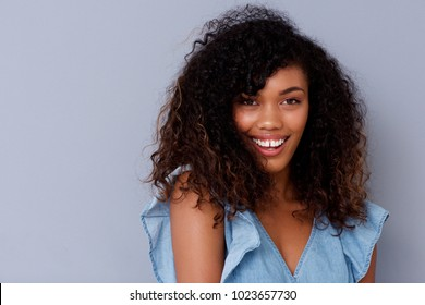 Close up portrait of beautiful young black woman smiling against gray wall
