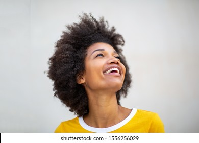 Close up portrait of beautiful young black woman laughing and looking up