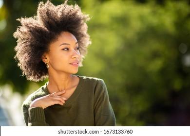 Close up portrait beautiful young black woman posing outside