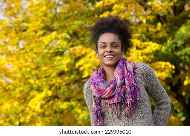 Close up portrait of a beautiful young black woman smiling outdoors in autumn