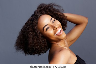 Close up portrait of beautiful young black woman laughing with hand in hair