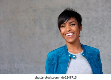 Close up portrait of beautiful young black woman with blue jacket smiling against gray background
