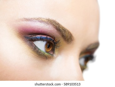 Close up portrait of a beautiful young blond model with bright make up. Close up of abstract multicolor make up. Makeup Pigment powder explosion