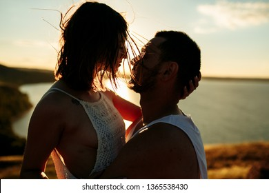 Close up portrait of a beautiful young couple waiting to kiss in their traveling time against sunset light.