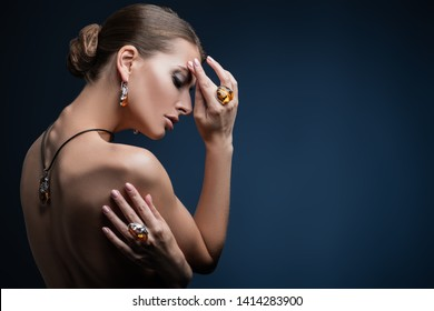 A close up portrait of a beautiful young dark-haired woman posing in the studio over the black background. Beauty, cosmetics, skincare, jewelry.