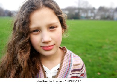 Close up portrait of a beautiful young girl with a gentle smiling expression, wearing a stripy knitted jumper while in a green grass park field during a winter autumn day outdoors.