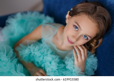 A close up portrait of a beautiful young girl with blue eyes, with make up and hairstyle in a lush turquoise dress