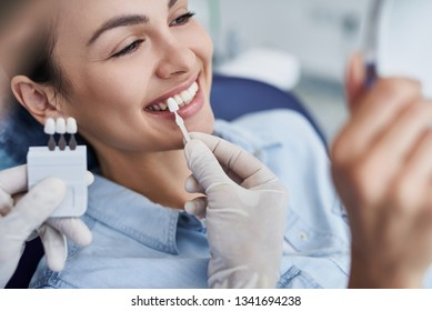 Nahaufnahme des Porträts einer schönen jungen Dame, die im Zahnstuhl sitzt, während die Stomatologen in sterilen Handschuhen mit Zahnproben Händen halten. Sie schaut in den Spiegel und lächelt