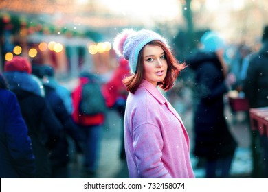 Close up portrait of a beautiful young model standing on a christmas background with bokeh lights and looking at camera. Magic warm new year photo.Cozy background. Happy woman.