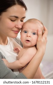 Close up portrait of beautiful young mother girl kissing her newborn baby.