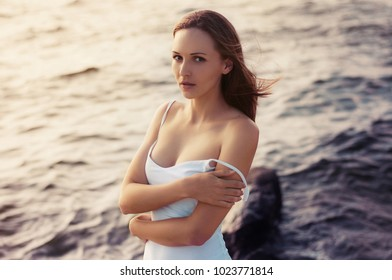 Close up portrait of beautiful young red hair woman in tight white dress with bare feet on beach  at sunset.