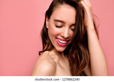 Close up portrait of beautiful young smiling woman with white teeth and pink lips with closed eyes on pink background