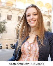 Close up portrait of a beautiful young tourist woman in a classic architecture city, wearing a light jacket and smiling at the camera.