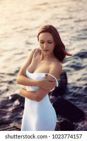 Close up portrait of beautiful young woman with red hair in tight white dress on the sunset beach.