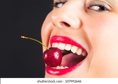 Close up portrait of beautiful young woman with cherry against black background.