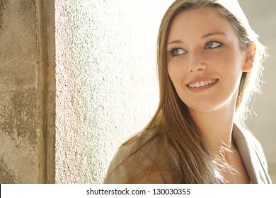 Close up portrait of a beautiful young woman tourist visiting a destination city and leaning on an old textured wall with the sun shining behind her, smiling.