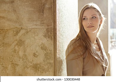Close up portrait of a beautiful young woman tourist visiting a destination city and leaning on an old textured column with the sun shining behind her, smiling.