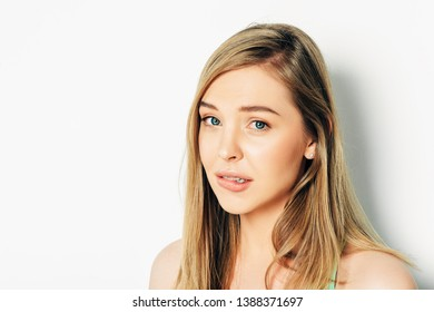 Close up portrait of beautiful young woman with blond hair and nude make up, guilty facial expression, biting lip