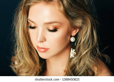 Close up portrait of beautiful young woman with blond hair and professional make up, posing on black background, looking down