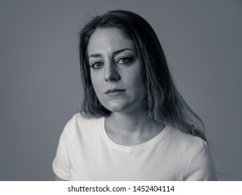 Close up portrait of beautiful young woman with sad mood looking miserable and melancholy. Human facial expressions and emotions, depression and mental health concept. Isolated on black and white.