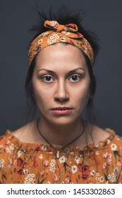 Close up portrait of beautiful young woman looking at the camera, vertical background. Attractive woman dressed in floral pattern dress wearing a head band - Beauty and fashion people studio shot.