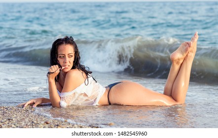 Close up portrait of beautiful young woman on the beach. Young woman model on the seashore. Summer time concept.