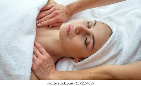 Close up portrait of a beautiful young woman with a towel on her head is receiving a neck massage and spa treatment for perfect skin in a luxury wellness center.