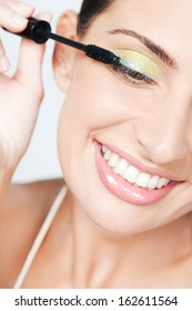 Close up portrait of a beautiful young woman applying party make up and glitter mascara on her eyelashes while smiling at home, against a white background, indoors.