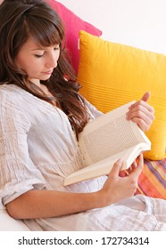 Close up portrait of a beautiful young woman on vacation, holding and reading a novel book while relaxing laying down on a colorful holiday sofa during a sunny summer day, interior.
