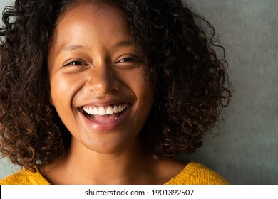 Close up portrait beautiful young woman with curly hair laughing
