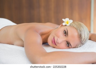 Close up portrait of a beautiful young woman lying on massage table at spa center