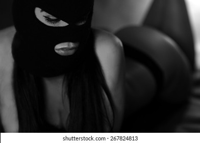 close up portrait of beautiful young woman in black sexy underwear, balaclava, lying on bed xxx