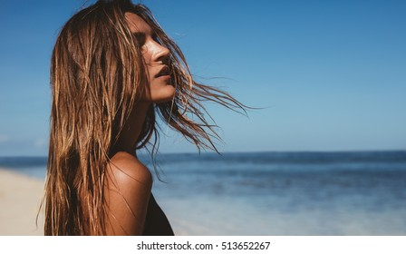 Close up portrait of beautiful young woman on the beach. Young caucasian female model on the sea shore.