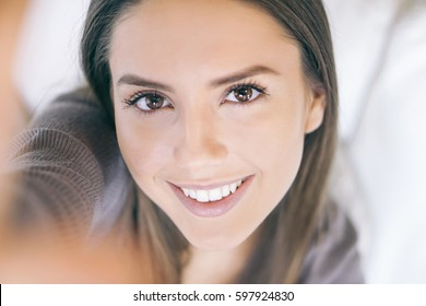 Close up portrait of a beautiful young woman taking a selfie while relaxing on the sofa at home - Stunning girl smiling to the mobile smartphone camera while taking a self portrait