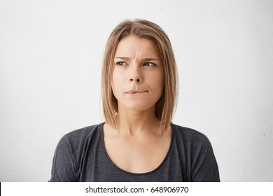 Close up portrait of beautiful young woman with bob hairstyle biting her lips and looking sideways with thoughtful doubtful expression as she has to make important decision, posing at blank wall