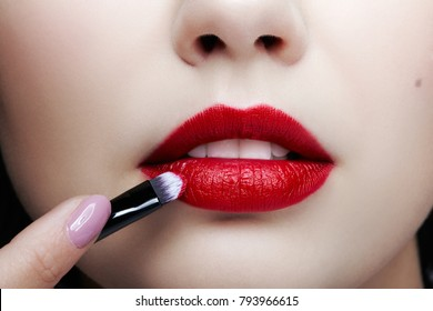 Close up portrait of beautiful young woman face. Female applying lips makeup with cosmetic brush