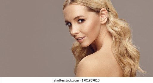Close up portrait of beauty smiling woman with long blond hair on free copy space. Attractive adult girl has a healthy skin.