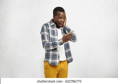 Close up portrait of black shocked hipster in stylish and trendy yellow pants, holding smartphone in one hand touching his head with another, looking scared and confused reading text message or e-mail
