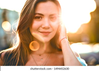 Close up portrait of blissful magnificent young elegant woman looking on camera, sting bright city sunlight , pure natural beauty face, brown eyes, long fluffy hairs.