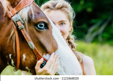 Close up portrait of blod smiling girl with blue eyes with her horse. Surrealistic effect with eyes. People and animals friendship concept.