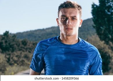 Close up portrait of a blonde, sweaty male runner (athlete). Running on an empty road in the woods.