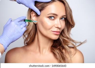 Nahaufnahme eines Porträts von blonden Frauen mit kosmetologischen Händen in der Nähe ihres Gesichts. Verfahren in den Bereichen Salon, Spa und Pflege