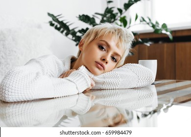 Close up portrait of blonde young woman wearing sweater and sitting at home