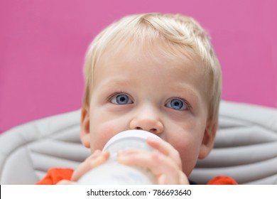 Close up portrait of blue-eyed toddler drinking his bottle.
