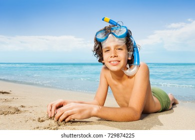 Close portrait of boy laying on the sand beach